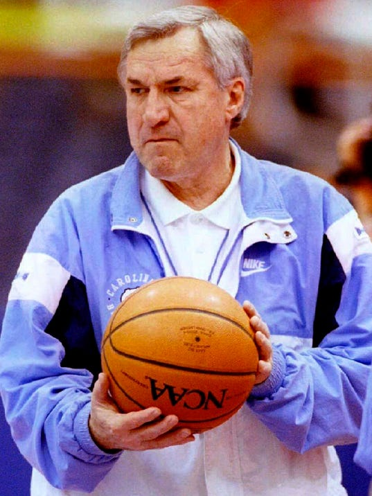 North Carolina head basketball coach Dean Smith carries the ball into the Tar Heel's practice in Syracuse, New York
