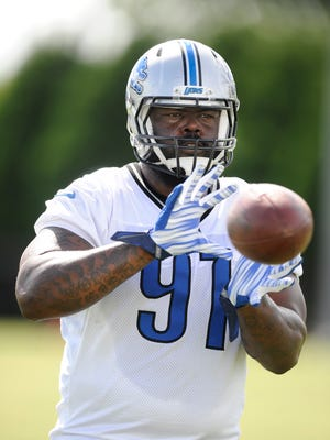 Lions defensive tackle A'Shawn Robinson catches some balls from the passing machine at the end of practice.