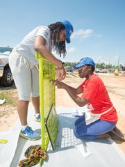 Americorps/Habitat volunteer Tuesday Donaldson, left, and Lucy Michelle assemble a part for the playground at Habitat for Humanity's Camshire Meadows community in Pensacola on Friday, April 13, 2018.