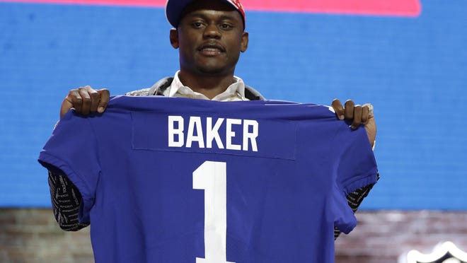 FILE - In this April 25, 2019, file photo, Georgia defensive back DeAndre Baker poses with his new jersey after the New York Giants selected him in the first round at the NFL football draft in Nashville, Tenn. Police in South Florida are trying to find Giants cornerback Baker and Seattle Seahawks cornerback Quinton Dunbar after multiple witnesses accused them of an armed robbery at a party. Miramar police issued arrest warrants for both men Thursday, May 14, 2020.