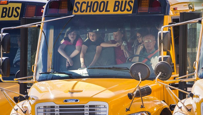 Students lean against the first seat of a school bus as they wait to be released on the first day back at Noblesville West Middle School, following Friday's shooting by a student that left a teacher and a student injured.