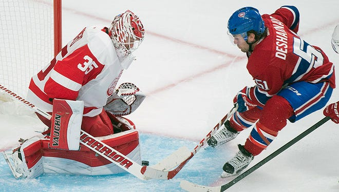 The Canadiens' David Desharnais, right, slides in on Red Wings goaltender Jimmy Howard during the third period of the Wings' 2-1 loss in overtime Tuesday in Montreal.