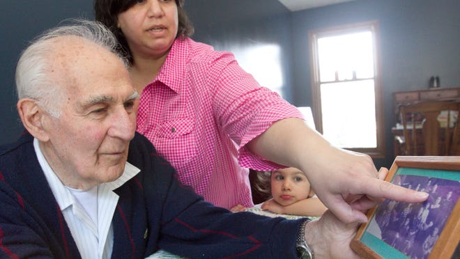 Andrea Rasizzi of Howell Township, standing, points to relatives that she's identified in a photo coincidentally containing family of Commerce Township resident George Mouradian. Their family members survived the Armenian genocide 100 years ago. Rasizzi's 4-year-old daughter, Lucine Rasizzi, looks on.