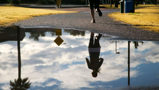 A jogger is reflected in a puddle along the path on the Old Cross Cut Canal in Phoenix on Dec. 22, 2016.