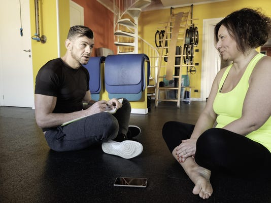 Fitness coach discusses the training program with his curvy client