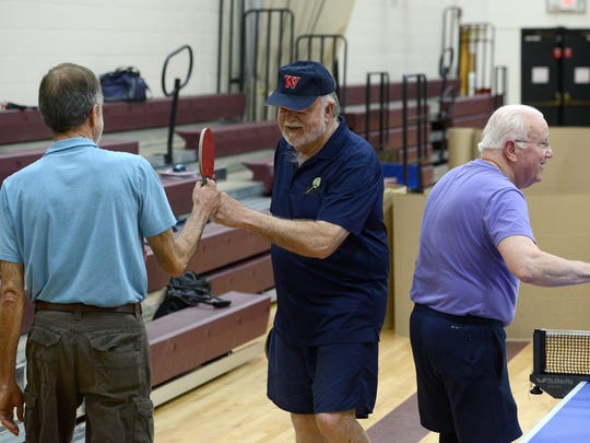 Don Davis, left, and Ralph Johnson, center, fist bump as Davis and Burm Snart switch sides of the table during a game of doubles table tennis during an open play night with the Asheville Table Tennis Club at the Montford Recreation Center on Monday. Although many club members are senior citizens, players Monday night ranged in age from 15 to 80.