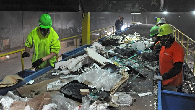 Workers sort on the new single-stream sorting conveyor system for commercial recycling at Nevada Recycling and Salvage.