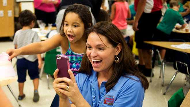 Lila Barson, 5, watches as her new kindergarten teacher, Janell Matos, takes a photo of her new classmate during an open house at Poinciana Elementary School in Naples on Aug. 13, 2015.