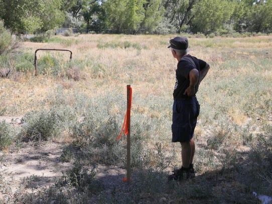 Artist Michael Darmody looks across a field at Berg