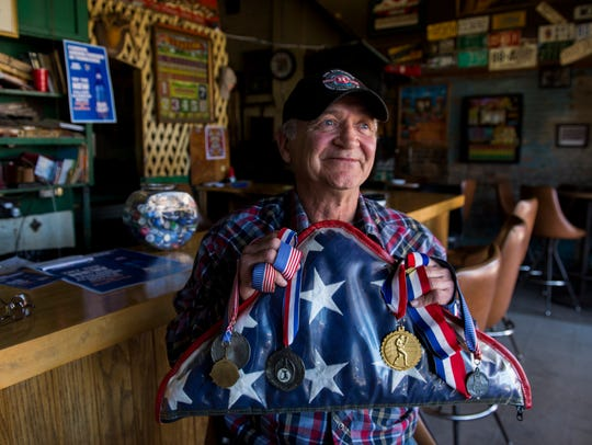 Neely Owens holds the folded American flag and all