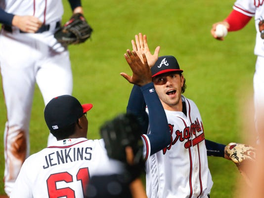 Atlanta Braves shortstop Dansby Swanson, center right,is greeted at the dugout by relief pitcher Tyrell Jenkins (61) after making a play in the field during the seventh inning of a baseball game against the Washington Nationals in Atlanta, Thursday, Aug. 18, 2016. (AP Photo/John Bazemore)