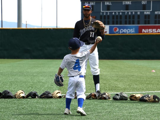 Nevada baseball coach T.J. Bruce's son Jaxon enjoys a game of catch with sophomore shortstop Jaylon McLaughlin during pregame warmups at Peccole Park in Reno on May 5, 2018.