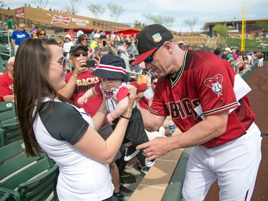 Diamondbacks manager Chip Hale signs the jersey of  Matthew Mellen, 3 months, as he is held by his mother, Alley Jens of Phoenix, before the spring training game against the Rockies at Salt River Fields at Talking Stick on Thursday, March 3, 2016.