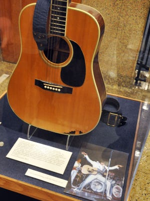 FILE - This April 22, 2013 file photo shows the slightly smashed acoustic guitar played by Elvis Presley during the final tour before his death in 1977 on display at the National Music Museum in Vermillion, S.D. The guitar may have to taken off display. A lawsuit filed in July 2014 in South Dakota is seeking to determine who is the legal owner of the guitar. Memphis-based guitarist Robert Johnson donated the Elvis guitar last year to the museum, but a man now claims he is the owner of the slightly smashed acoustic guitar. (AP Photo/Dirk Lammers, File)