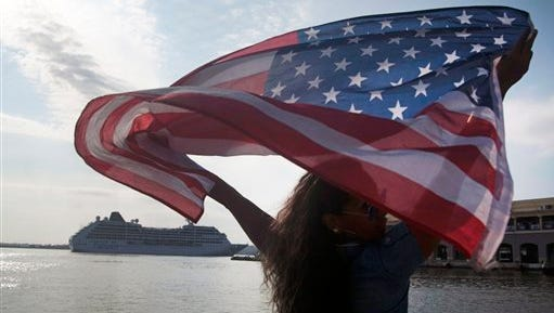 Yaney Cajigal waves a U.S. flag as she watches the arrival of Carnival's Adonia cruise ship from Miami in Havana, Cuba, Monday, May 2, 2016. The Adonia's arrival is the first step toward a future in which thousands of ships a year could cross the Florida Straits, long closed to most U.S.-Cuba traffic due to tensions that once brought the world to the brink of nuclear war. (AP Photo/Fernando Medina)