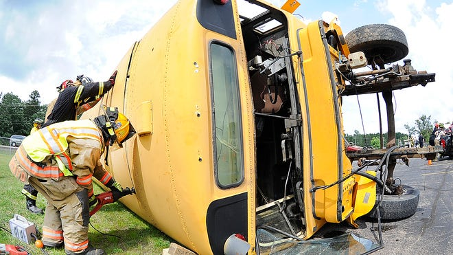 Vesper Fire Department Capt. Dustin Brehm uses a saw to cut into the top of a school bus on its side Saturday during the 2014 Wood County Extrication Symposium at the Saratoga Town Hall parking lot.