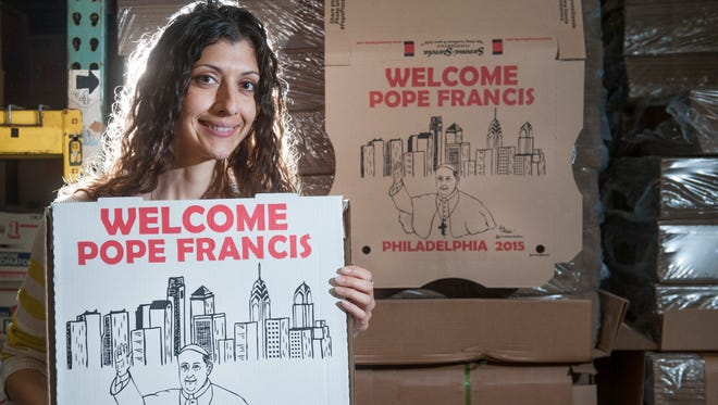 Amanda Farese, Director of Marketing for Savona Stavola and self taught artist, holds the pizza box that welcomes Pope Francis, that she designed.
