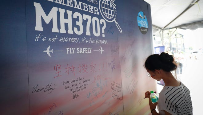 A girl writes a condolence message during the Day of Remembrance for MH370 event in Kuala Lumpur, Malaysia on March 3, 2018.