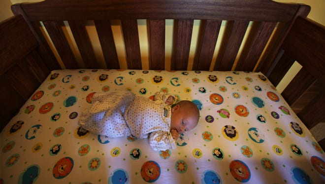 A newborn sleeps in his crib, which is properly outfitted for his safety.