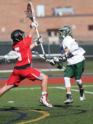 From right, Yorktown's Shane Dahike (29) fires a shot for a first half goal in front of  Somers' goalie Tyler Carr (5) during a  lacrosse game at Yorktown High School April 19, 2016. Yorktown won the game 11-3.
