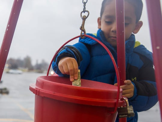 Alex Martinez, 5, donates money into the Salvation Army red bucket outside K-Mart in Henderson on Monday afternoon. He learned that even though he has lots of toys at home there are some kids that don't have any at all.