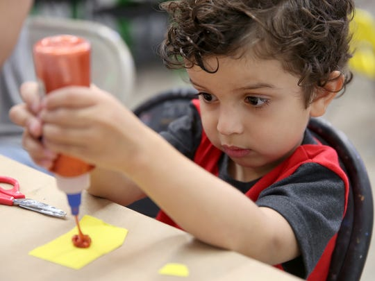 Zander Martinez, 3, concentrates on his glue while working on an art project during the Family Lunar New Year event at the San Angelo Museum of Fine Arts on Saturday, Feb. 11, 2017.