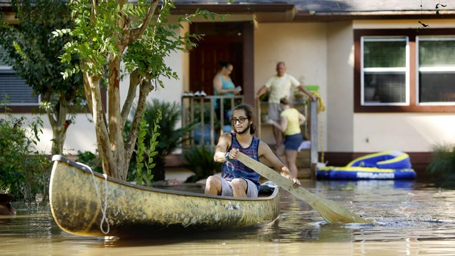 Gianni Pena paddles a canoe through the flood waters surrounding his families home in the Hills of Santa Fe neighborhood after Hurricane Irma in September 2017. A new national mapping of flood risk shows many more properties could experience flooding than are indicated by federal maps.