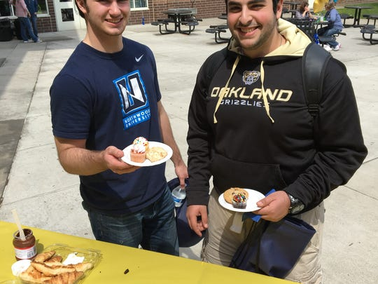 Two HHS seniors enjoy some cake during college signing day on Tuesday.