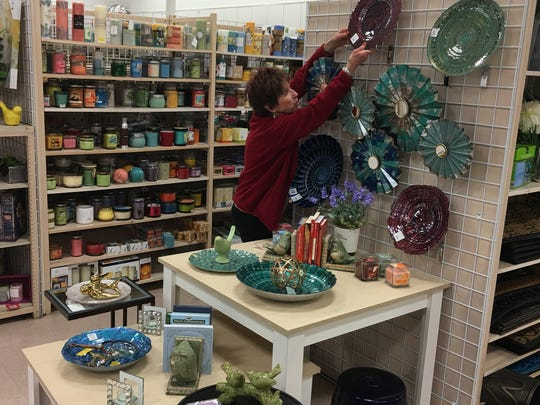 "Bobbie Brister adjusts one of her patented ""end cap"" displays that help brighten the sales floor at Burkes."