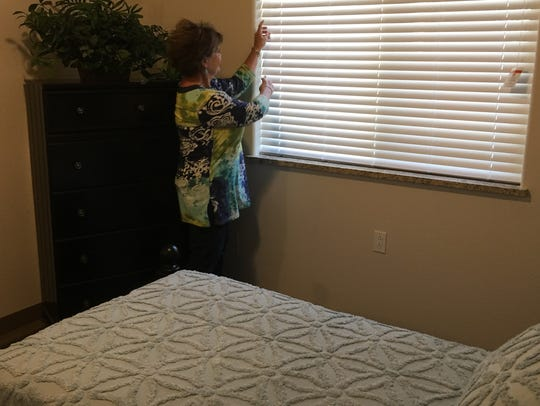Administrator Barbara Watson adjust blinds in one of