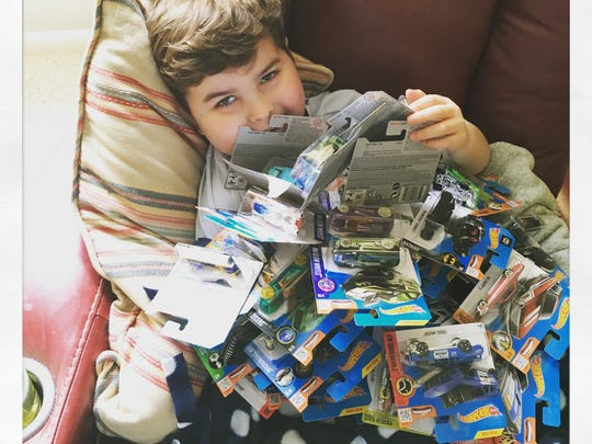 Brooks Blackmore is covered in Hot Wheels during his illness. The little boy died in 2016, but his little cars bring smiles to young and old around the world.