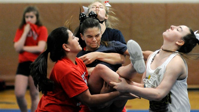 Roy C. Ketcham High School varsity cheerleader Taylorann Torre lands in the arms of fellow varsity cheerleaders at practice on June 12 in Wappingers Falls. Catching her, from left, are Sabrina Polini,   Courtney Tefft and Rosie Gramuglia.