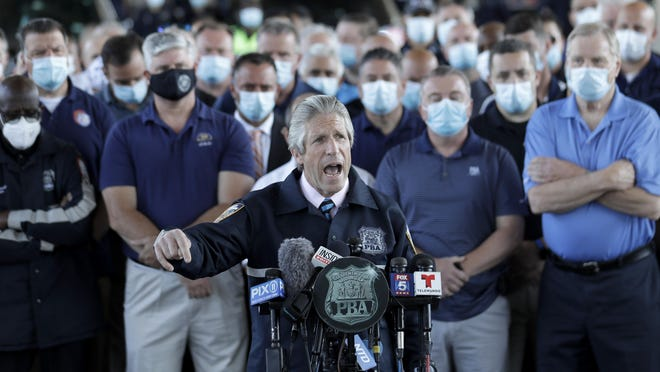 Surrounded by law enforcement and supporters, New York City PBA President Pat Lynch, center, speaks during a news conference in New York, Tuesday, June 9, 2020.