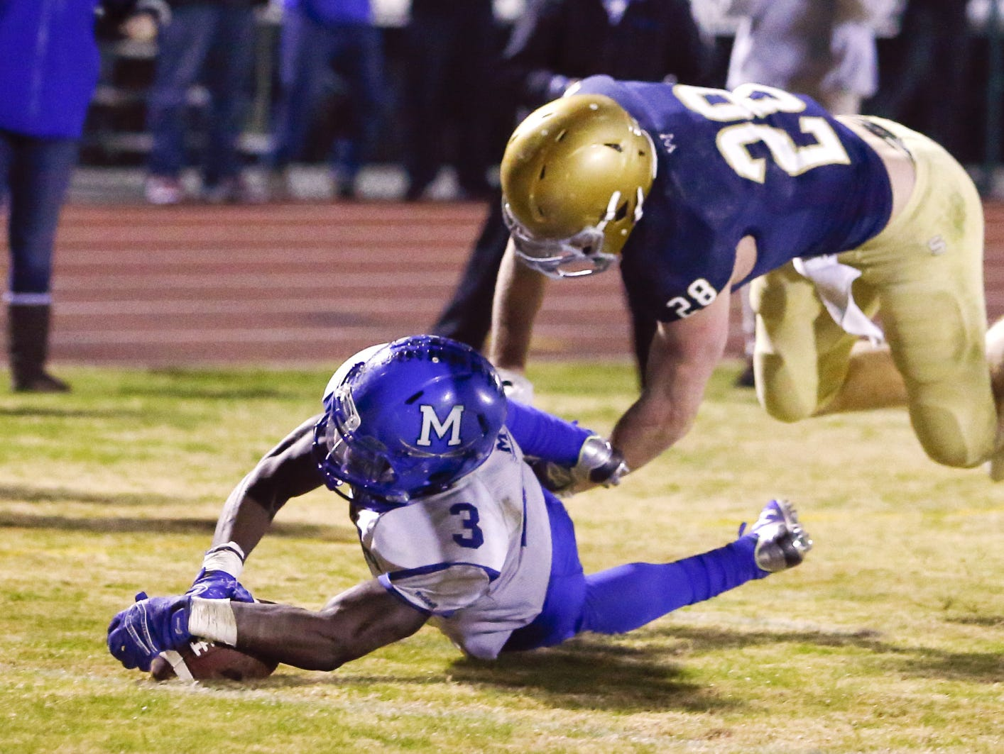 Middletown's Kedrick Whitehead falls on his own fumble for touchdown as Salesianum's Colby Reeder defends in the first quarter of a DIAA Division I state tournament semifinal at Baynard Stadium Friday.