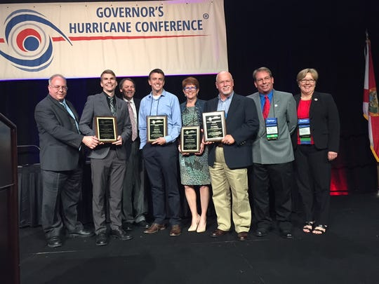 Logan Hemenway of Brevard EOC; Will Ulrich of NWS Melbourne; Kimberly Prossser of Brevard EOC; and Don Walker of Brevard EOC are presented with Public Information Awards at the Governor's Hurricane Conference in Orlando on Thursday.