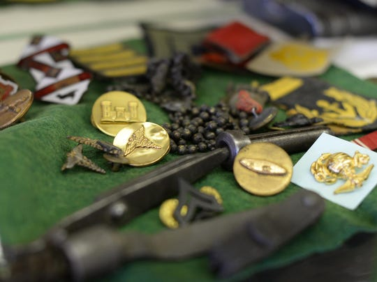86-year-old Robert Brien keeps a case of mementos from his WWII service at his shop.