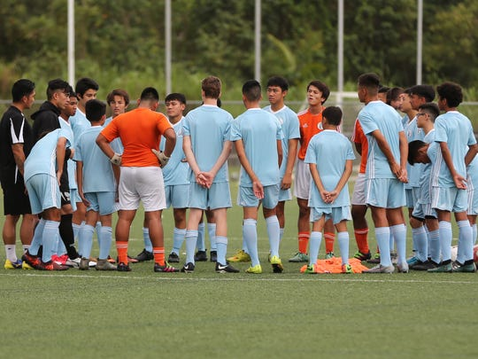 The Guam U15 Boys National Team training squad huddle to receive instructions from Head Coach Dominic Gadia and Goalkeeper Coach Ross Awa, during a recent training session at the Guam Football Association National Training Center. The team will be headed to Beijing, China PR next month for the EAFF U-15 Boys' Tournament 2018.