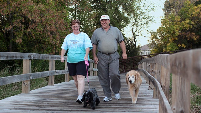 Laurie and Jeff Schuttey walk their dogs Pixie (left) and Hunter at the Rusch Park by the Sawyer Creek Nature Preserve in this 2009 file photo.