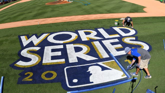 Workers put the finishing touches on the World Series logo and the field before today's workouts one day prior to game one of the World Series between the Los Angeles Dodgers and the Houston Astros at Dodger Stadium in Los Angeles.