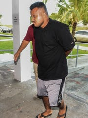 James Niosy, front, is escorted into the Guam Police Department Hagåtña precinct upon his arrest on Wednesday, Jan. 11, 2017. Niosy was arrested for allegedly falsely reporting that his 3-year-old daughter was in his car which was stolen.