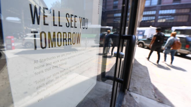 A sign explaining why the Starbucks is closed hangs on the window of a Starbucks in New York.
