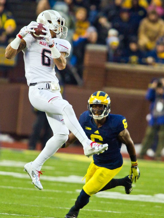 Maryland wide receiver Deon Long (6) makes a catch over Michigan defensive back Raymon Taylor (6) in the second quarter of an NCAA college football game in Ann Arbor, Mich., Saturday, Nov. 22, 2014. (AP Photo/Tony Ding)