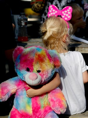 Aprilynn Murphy enjoys a snack with her family and new stuffed friend at the Portland Festival. 