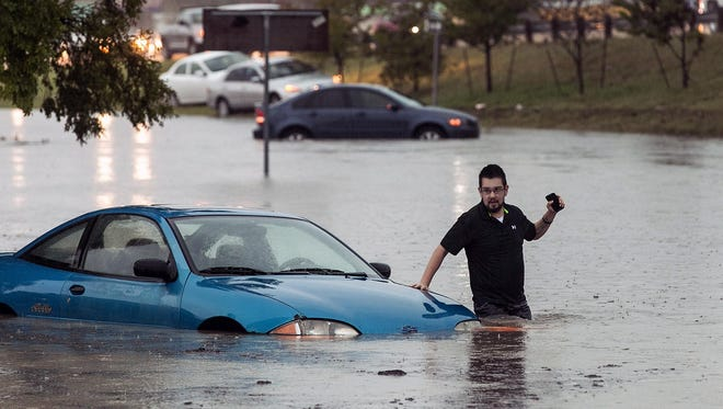 Mike Stoner gets out of his flooded car Friday in San Marcos, Texas.