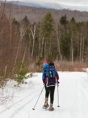 A woman snowshoes with her toddler, near Mendon Brook in the Green Mountains near Shrewsbury.