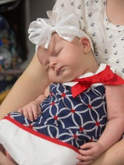Sawyer Justus, 7 weeks old, sleeps in her mother's arms. Each year, World Breastfeeding Week celebrates the Innocenti Declaration to protect, promote and support breastfeeding.