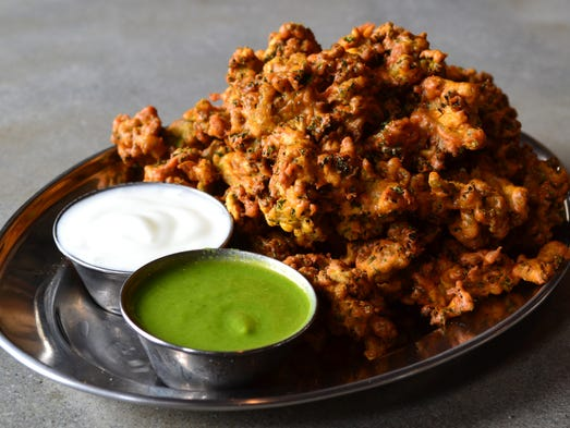 The fried kale pakora served at Chai Pani in Asheville, N.C., comes coated in curry chickpea batter and is served with green chutney and sweet yogurt.