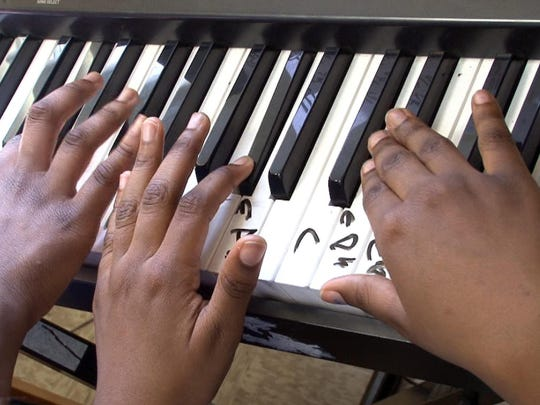 Students play a piano in the music room at the Hope Academy of Asbury Park Wednesday, March 16, 2016.