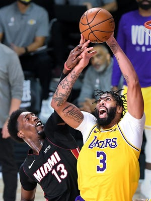 The Los Angeles Lakers' Anthony Davis (3) grabs a rebound against the Miami Heat's Bam Adebayo (13) during the fourth quarter in Game 4 of the NBA Finals at AdventHealth Arena at the ESPN Wide World Of Sports Complex on Tuesday, Oct. 6, 2020, in Lake Buena Vista, Fla.
