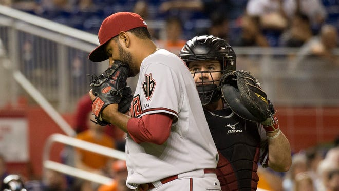 Arizona Diamondbacks relief pitcher Enrique Burgos, left, and catcher Tuffy Gosewisch talk on the mound during the ninth inning of a baseball game against the Miami Marlins in Miami, Tuesday, May 19, 2015. The Diamondbacks won 4-2.